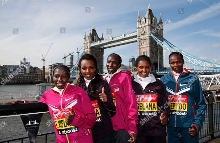 Elite marathon runners from left, Florence Kiplagat of Kenya, Tirunesh Dibaba of Ethiopia, Edna Kiplagat of Kenya, Tiki Gelana of Ethiopia, and Priscah Jeptoo of Kenya, pose for photographers, backdropped by Tower Bridge during a photocall in London, . The London marathon takes place on Sunday, April 13