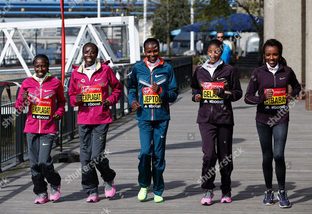 Elite marathon runners from left to right, Florence Kiplagat, Edna Kiplagat, Priscah Jeptoo, all from Kenya, Tiki Gelana and Tirunesh Dibaba, both from Ethiopia, perform a posed jog for photographers during a photocall in London, . The London marathon takes place on Sunday April 13, 2014