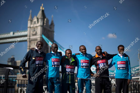Elite male marathon runners, from left, Uganda's Stephen Kiprotich, Kenya's Emmanuel Mutai, Ethiopia's Tsegaye Kebede Kenya's Geoffrey Mutai, Ethiopia's Ibrahim Jeilan and Tsegaye Mekonnen pose for photographers backdropped by Tower Bridge during a photocall in London, . The London marathon takes place on Sunday