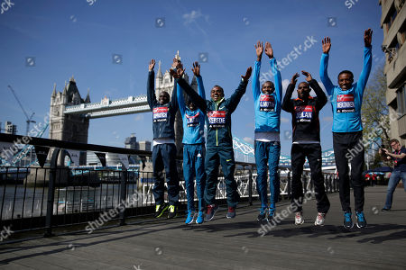 Elite male marathon runners, from left, Uganda's Stephen Kiprotich, Kenya's Emmanuel Mutai, Ethiopia's Tsegaye Kebede, Kenya's Geoffrey Mutai, Ethiopia's Ibrahim Jeilan and Tsegaye Mekonnen jump at the request of photographers as they pose backdropped by Tower Bridge during a photocall in London, . The London marathon takes place on Sunday