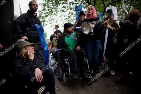 A demonstrator in a wheelchair speaks out into a megaphone against the short term loans company Wonga outside a building that houses their offices in London, during a May Day protest, . This year's annual May Day protest had special emphasis on paying tribute to the lives of Bob Crow, the late general secretary of Britain's Rail, Maritime and Transport union and socialist politician Tony Benn who both died recently