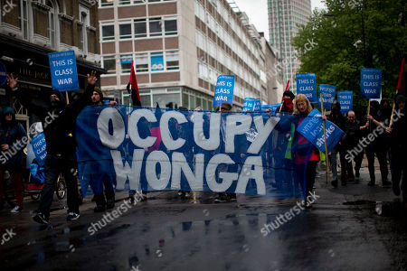 Demonstrators march through central London with a banner and placards against the short term loans company Wonga en route to a building that houses their offices in London, during a May Day protest, . This year's annual May Day protest had special emphasis on paying tribute to the lives of Bob Crow, the late general secretary of Britain's Rail, Maritime and Transport union and socialist politician Tony Benn who both died recently