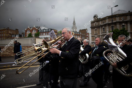 A brass band from Britain's Rail, Maritime and Transport union takes part in a May Day Trades Unions workers' rights protest march in London, . This year's annual May Day protest had special emphasis on paying tribute to the lives of Bob Crow, the late general secretary of Britain's Rail, Maritime and Transport union and socialist politician Tony Benn who both died recently