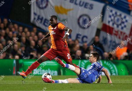 Chelsea's Oscar, right slides into tackle Galatasaray's Emmanuel Eboue during the Champions League last 16 second leg soccer match between Chelsea and Galatasaray at Stamford Bridge stadium in London