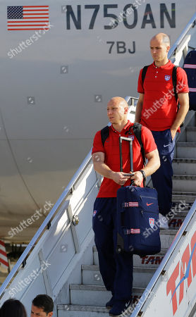 Brad Guzan, Michael Bradley CORRECTS THE NAME OF THE PLAYER IN THE FOREGROUND TO BRAD GUZAN, NOT BRAD FRIEDEL AS ORIGINALLY SENT - United States' national soccer team goalkeeper Brad Guzan, bottom, and Michael Bradley arrives at the Sao Paulo International airport in Brazil, . The U.S. team arrived in Sao Paulo to continue their preparations for the upcoming Brazil 2014 World Cup, which starts on June 12