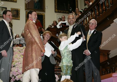 Pam Allen, Registrar for nearby Northampton conducts the civil partnership ceremony for Author Andrew Solomon and John Habich on the grand staircase at Althorp whilst one of the page boys shows the certificate to the guests