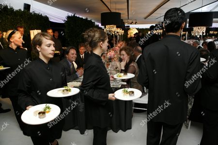 Dinner is served in a purpose built marquee sumptuously decorated in black and white with pink roses and elaborate place settings, and with a central rostrum for the orchestra (and for speakers), surrounded by a black and white dance floor