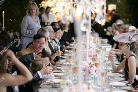 Stock Photo of Dinner is served in a purpose built marquee sumptuously decorated in black and white with pink roses and elaborate place settings, and with a central rostrum for the orchestra (and for speakers), surrounded by a black and white dance floor
