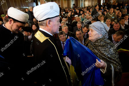 An elderly woman holds a Ukrainian flag in front of Russia's top Muslim Cleric Ravil Gainutdin, center, during the Crimean Tatar Qurultay, a religious congress, in Bakhchysarai, Crimea, . The Crimean Tatar Qurultay, a religious congress will determine whether the Tatars will accept Russian citizenship and the political system that comes with it, or remain Ukrainian citizens on Russian soil
