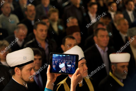 A Crimean Tatar's woman films as Russia's top Muslim Cleric Ravil Gainutdin, foreground center, deputy chairman of Russia Muftis Council Rushan hazrat Abbyasov, foreground left, and Mufti of Crimean Muslims Emirali Ablayev, foreground right, attend the Qurultay, a religious congress, in Bakhchysarai, Crimea, . The Crimean Tatar Qurultay, a religious congress will determine whether the Tatars will accept Russian citizenship and the political system that comes with it, or remain Ukrainian citizens on Russian soil