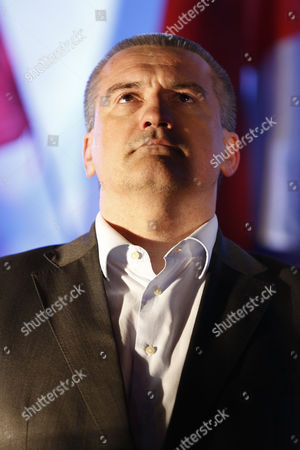The head of Crimea's unrecognized Russian-backed government Sergey Aksyonov looks on during celebrations to mark the switch to Moscow time near a clock tower at railway station in Simferopol, Crimea, . Sevastopol and Crimea switched to Moscow time at 2 a.m. on Sunday, March 30, advancing the clocks by two hours