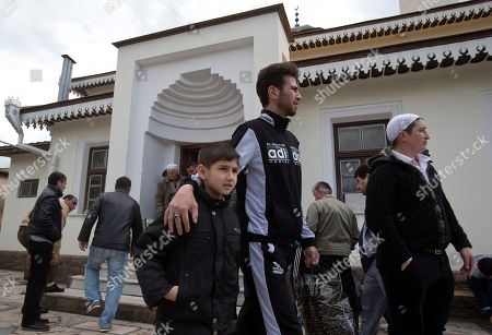 Believers walk after praying in a mosque in Simferopol, Crimea, . Russia's top Muslim Cleric Ravil Gainutdin is in Crimea to attend Saturday's Crimean Tatar Qurultay, a religious congress that will determine whether the Tatars will accept Russian citizenship and the political system that comes with it, or remain Ukrainian citizens on Russian soil
