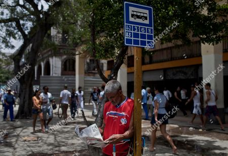 A man reads a copy of Cuba's state newspaper Granma while waiting for the bus in Havana, Cuba, . Cuba's best-known blogger Yoani Sanchez and her husband Reinaldo Escobar say they will start publishing the country's first major independent general-interest newspaper in more than 50 years on Wednesday, in a move that will test both the government's openness to free expression and the dissident's ability to build a following inside her country