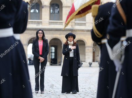 Argentine President Cristina Fernandez, right, stands in front of the French flag as the national anthems are being played, after been welcome by French Francophony Minister Yamina Benguigui, left, at the Invalides in Paris, . Cristina Fernandez arrived Tuesday for an official visit in France