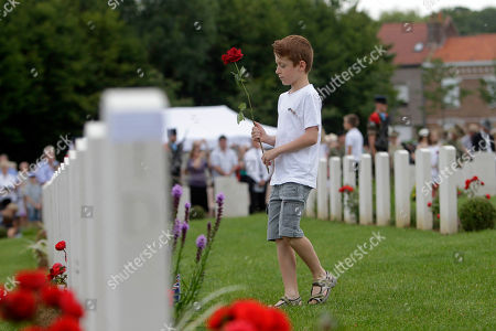 A young French boy lays a flower on a grave during the Headstone Dedication for twelve Australian World War I soldiers identified, at the Fromelles (Pheasant Wood) Military Cemetery, in Fromelles, northern France, Saturday, July 19, 2014. The twelve Australians identified are: Private David Samuel Anderson 54th Battalion, Private Vinton Battam Baker 55th Battalion, Private Jack Marchmont Campbell 54th Battalion, Private William Thomas Connoly 54th Battalion, Private John Edwin Crocker 32nd Battalion, Private Willie Hilton Doust 54th Battalion, Private Frederic James Gleen 30th Battalion, Private Sidney John Gray 54th Battalion, Private Reginald Theodore Griffen 32nd Battalion, Private Adolf Thompson Knable 32nd Battalion, Private Joseph Edward Lee 60th Battalion, Private Archie McDonald 31st Battalion, Private Ernest Robert Olover 29th Battalion, Private Edgar William Parham 32nd Battalion, Private William Henry Christian Rose 55th Battalion, Private Gordon Thomas Smith 29th Battalion, Private Herbert Newey ST.Smith 32nd Battalion, Private Percy Weakley 31st Battalion, Private Albert Williamson 54th Battalion and Private Harold George Woodman 31st Battalion