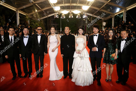 Producer Zhang Zhao, second left, actor Chen Daoming, third left, actress Gong Li, fourth left, director Zhang Yimou, center, actress Zhang Huiwen, fourth from left, and unidentified guests pose for photographers as they arrive for the screening of Coming Home (Gu Lai) at the 67th international film festival, Cannes, southern France