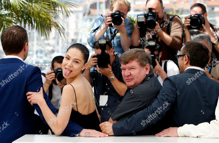 Actress Elena Lyadova, second from left, sticks her tongue out as she poses for photographers alongside actor Vladimir Vdovichenkov, left, actor Roman Madianov, second from right, and director Andrey Zvyagintsev, right, during a photo call for Leviathan at the 67th international film festival, Cannes, southern France