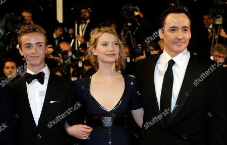 From left, actor Evan Bird, actress Mia Wasikowska and actor John Cusack pose for photographers as they arrive for the screening of Maps to the Stars at the 67th international film festival, Cannes, southern France