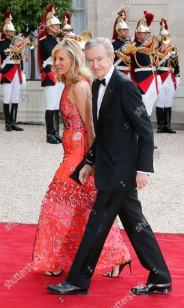 Bernard Arnault Chairman & Chief executive officer of LVMH luxury group and his wife Helene Arnault arrive at the Elysee Palace for a State dinner in honor of Queen Elizabeth II, hosted by French President Francois Hollande, Paris. Queen Elizabeth, Prince Charles and other royalty are on a three-day state visit to France to mark the 70th anniversary of the D-Day landings in Normandy during WWII