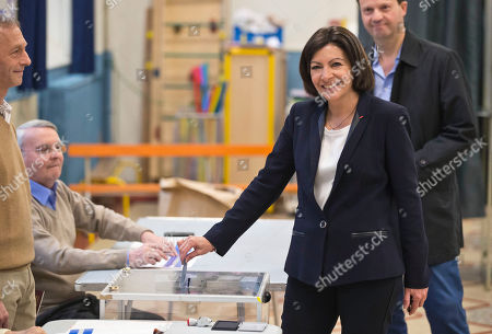 Anne Hidalgo, Jean-Marc Germain Socialist candidate for the mayor of Paris, Anne Hidalgo poses for photographers as she casts her ballot during the municipal elections in Paris, . Voters in Paris and across France are going to the polls Sunday in municipal elections seen as a referendum on embattled President Francois Hollande's first two years in office. One bright spot for Hollande is the capital, where Hidalgo is favorite to defeat rival Nathalie Kosciusko-Morizet and keep Paris in Socialist control for another six-year term. Behind her is her husband Jean-Marc Germain