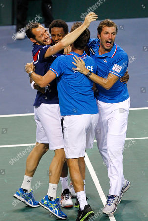 France's Gael Monfils celebrates with teammates Michael llodra, left, Julien Benneteau, right, and team coach Arnaud Clement, center, after winning his singles match against German Peter Gojowczyk, in the quarterfinals of the Davis Cup in Nancy, eastern France, . France qualifies for the semifinals with a 3-2 score