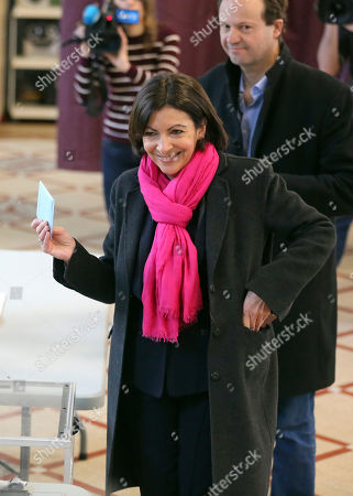Anne Hidalgo, Jean-Marc Germain Socialist candidate for the mayor of Paris, Anne Hidalgo, shows her ballot before voting for the municipal elections in Paris, . Voters across France are casting ballots in the first round of municipal elections Sunday as two female candidates compete to run Paris City Hall and far right candidates are hoping for a strong showing. Standing behind her is her husband Jean-Marc Germain