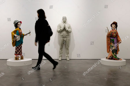 """A journalist walks past """"The Future Pharrell"""", center, a 2014 resin and shattered glass sculpture by US artist Daniel Arsham, and """"Kokemono"""", left and right, mixed media sculptures by Japanese artist Chiho Aoshima, during the presentation of the exhibition """"GIRL"""" curated by US singer Pharrell Williams at the Perrotin Gallery in Paris, . Williams curated an exhibition encompassing around 40 art pieces, presenting their visions of femininity, muses, female creativity and freedom. The show opens on May 27 and runs through June 27, 2014"""