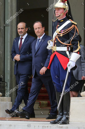 French President Francois Hollande, centre, leaves with President of the Syrian National Coalition Ahmad Al-Assi A-Jarba, following their meeting at the Elysee Palace in Paris