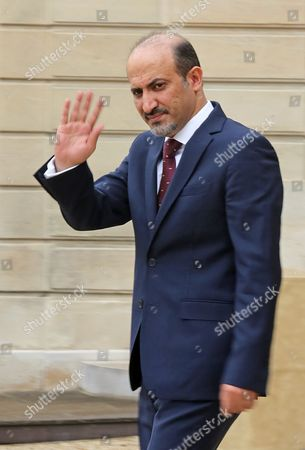 President of the Syrian National Coalition Ahmad Al-Assi A-Jarba waves to reporter as he leaves the Elysee Palace, following his meeting with French President Francois Hollande in Paris