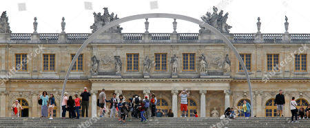 Visitors walk under The Arch of Versailles, a work of art by Korean artist Lee Ufan, displayed in the gardens of the Versailles Castle, west of Paris, . Korean painter and sculptor Lee Ufan is this summer's guest artist in Versailles. Ten new works have been placed throughout the palace and gardens. The exhibition lasts until Nov. 2014