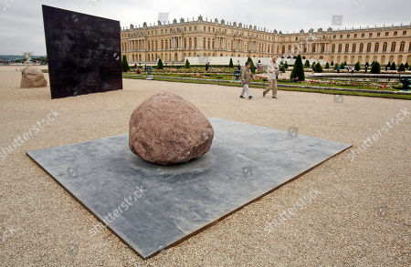Two visitors walk past Dialogue X, a work of art by Korean artist Lee Ufan, displayed in the gardens of the Versailles Castle, west of Paris, . Korean painter and sculptor Lee Ufan is this summer's guest artist in Versailles. Ten new works have been placed throughout the palace and gardens. The exhibition lasts until Nov. 2014