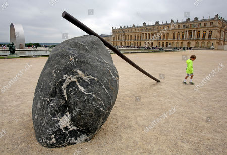 A child walks past The Cane of Titan, a work of art by Korean artist Lee Ufan, displayed in the gardens of the Versailles Castle, west of Paris, . Korean painter and sculptor Lee Ufan is this summer's guest artist in Versailles. Ten new works have been placed throughout the palace and gardens. The exhibition lasts until Nov. 2014