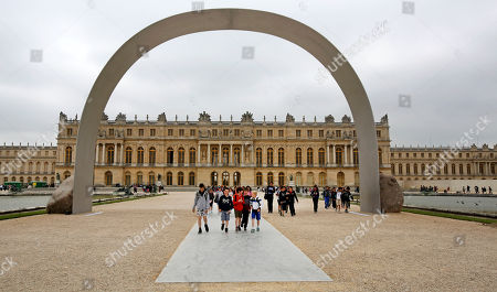 Young visitors walk under The Arch of Versailles, a work of art by Korean artist Lee Ufan, displayed in the gardens of the Versailles Castle, west of Paris, . Korean painter and sculptor Lee Ufan is this summer's guest artist in Versailles. Ten new works have been placed throughout the palace and gardens. The exhibition lasts until Nov. 2014
