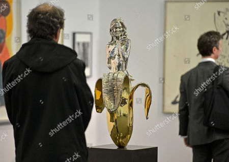A visitor watches a girl in a banana by artist Mel Ramos at the fair Art Cologne, in Cologne, Germany