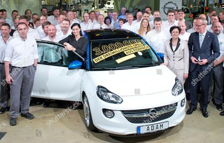 Karl-Thomas Neumann, Chairman of the Board of Opel AG, second right, Christine Lieberknecht, governor of the German state Thuringia, fourth of right, and employees stand besides an Opel Adam, which is the three millionth car produced in the German car company Opel Eisenach GmbH, owned by General Motors, in Eisenach, Germany