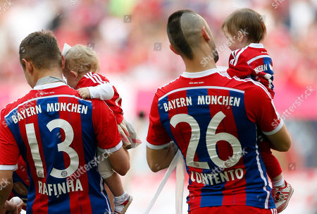 Bayern's Rafinha of Brazil, left, and teammate Bayern's Diego Contento hold their children after winning the German Soccer Championships after the season's last match between FC Bayern Munich and VfB Stuttgart, in Munich, southern Germany