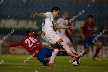 Carlos Figueroa, top, of Comunicaciones is tackled by Cristian Jimenez of Municipal during the first leg of the Guatemalan soccer league final in Guatemala City, . The Guatemalan soccer federation decided to play the matches of the final, in front of empty stadiums after Kevin Diaz, a 17-year-old fan of Comunicaciones was allegedly killed in April by supporters of Municipal before the start of a game