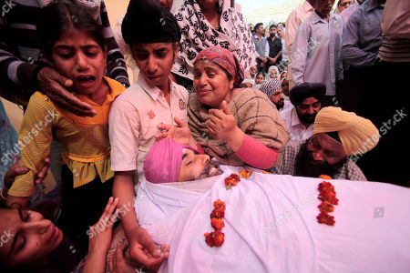 Wife and children of driver Tarsem singh, who was taken hostage and killed, weep near his body before his cremation at Kotli Mirdian, about 39 kilometers (24 miles) from Jammu, India, . Gunmen disguised as Indian soldiers hijacked a car Friday in Indian-controlled Kashmir, killing the driver and a passenger, and used it to try to storm an Indian army artillery unit, triggering a firefight that left four more people dead, authorities said