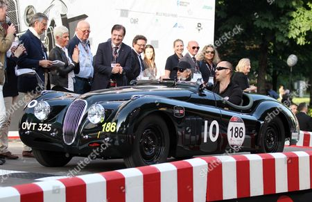 """Jay Leno, Ian Callum British actor Jeremy Irons, left, and Charlie Turner sit in the cockpit of their Jaguar at the start of the """"Mille Miglia"""" historical endurance for classic and vintage cars race, in Brescia, Italy"""