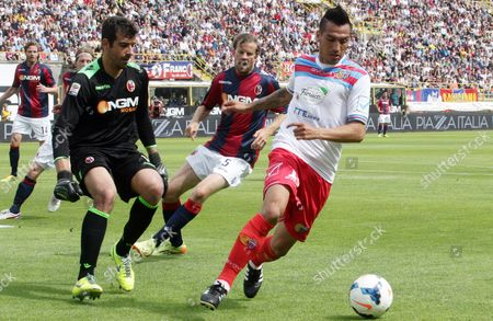 Catania's Luciano Fabian Monzon, right, tries to dribble Bologna goalkeeper Gianluca Curci during the Italian Serie A soccer match between Bologna and Catania at Renato Dall' Ara stadium in Bologna, Italy