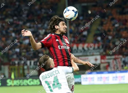AC Milan defender Cristian Zaccardo, right, challenges for the ball with Sassuolo forward Gaetano Masucci during the Serie A soccer match between AC Milan and Sassuolo at the San Siro stadium in Milan, Italy