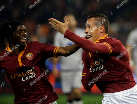 Stock Image of Roma's Rodrigo Taddei, right, celebrates with teammate Gervinho after scoring during a Serie A soccer match between Roma and Atalanta in Rome's Olympic stadium