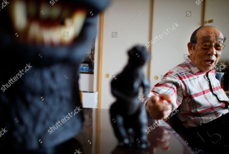 Stock Image of Original Godzilla suit actor Haruo Nakajima, who has played his role as the monster, points a figure of the monster he made for the movie, as he speaks during an interview at his home in Sagamihara, near Tokyo. Nakajima, 85, was a stunt actor in samurai films, when he was approached to take the Godzilla role. He had to invent the character from scratch, and went to the zoo to study the way elephants and bears moved
