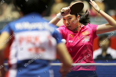 Stock Picture of Li Xiaoxia, Ri Myong Sun Li Xiaoxia, right, of China serves the ball during her round robin match of the World Team Table Tennis Championships against Ri Myong Sun, left, of North Korea in Tokyo