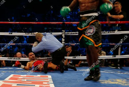 """Nicholas Walters, Vic Darchinyan Vic """"Raging Bull"""" Darchinyan of the U.S., left, falls after being hit by Nicholas """"The Axe Man"""" Walters of Jamaica during the WBA World Featherweight Title boxing match in Macau"""