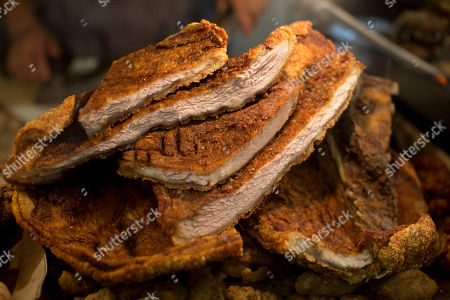 Thick slabs of kastakan, Yucatecan pork belly fried crisp in its own fat are for sale at the Central Market in Merida, Mexico. American celebrity chef Jeremiah Tower said that he visits the city's central covered market in the mornings and spends his afternoons working on a new book, an illustrated dictionary of the historical intersection of food and sex
