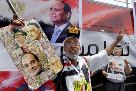 An Egyptian supporter of Abdel-Fattah el-Sissi, the nation's former military chief, wears a toy tank on his head as he holds a poster showing him with images of late presidents Anwar Sadat, top left, Gamal Abdel Nasser, top right and Egypt's interim President Adly Mansour, bottom right, during a celebration in Tahrir Square, in Cairo, Egypt, . Nearly a year after he ousted Egypt's first freely elected president, former military chief Abdel-Fattah el-Sissi was elected president by a landslide of 92 percent of the vote, according to unofficial results released by his campaign Thursday. But questions over the authorities' drive to boost turnout threatened to stain his victory
