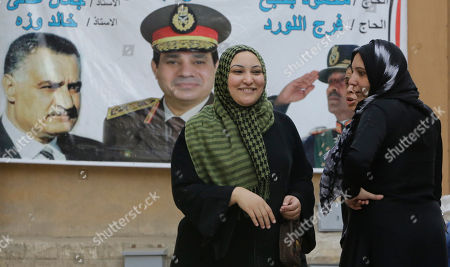 Egyptian women chat in front of a banner showing presidential candidate Abdel-Fattah el-Sissi, the country's former military chief, center, along with late presidents Anwar Sadat, right, and Gamal Abdel-Nasser, left, two days before presidential elections in Cairo, Egypt, . Considered all but certain to win is el-Sissi, the man who removed the former president, Mohammed Morsi. El-Sissi, who for the past 10 months has been the most powerful figure in Egypt, faces one other candidate in the race, leftist politician Hamdeen Sabahi, who finished third in the 2012 presidential election