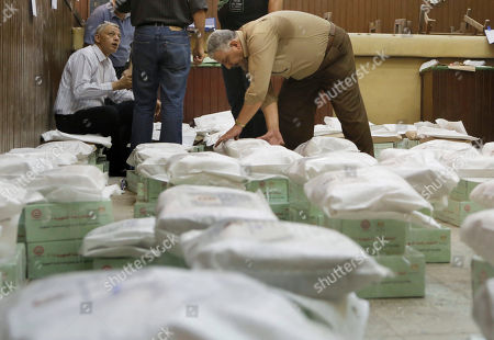 An Egyptian worker arranges boxes of ballots at the Giza courthouse a day before the country's two-day presidential elections begins, in Cairo, Egypt, . Egypt's interim President Adly Mansour has urged Egyptians to come out and vote in this week's presidential election, saying the vote will shape the nation's future