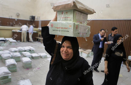 An Egyptian worker carries boxes of ballots at the Giza courthouse in Cairo, Egypt, a day before the country's presidential elections. Egypt's interim President Adly Mansour has urged Egyptians to come out and vote in this week's presidential election, saying the vote will shape the nation's future